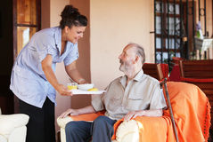 Senior home care. Elderly senior being brought meal by carer or nurse, care at home