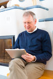 Senior at home in front of fireplace. Quality of life - Older man or Pensioner sitting at home in front of the furnace, writing emails on the tablet computer or Stock Photography
