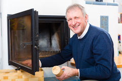 Senior at home in front of fireplace Royalty Free Stock Photos