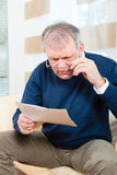 Senior at home receiving negative message Royalty Free Stock Images