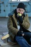 Senior homeless man eating an apple Stock Photo