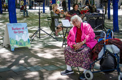 Senior homeless woman listens to music in a Seattle park. Senior homeless woman listens to the Summer Januaries string duo among the blue trees in Westlake Park Royalty Free Stock Photography
