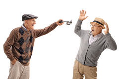 Senior honking a horn and scaring another senior. Isolated on white background Stock Image