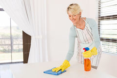 Senior housewife wiping table Stock Images