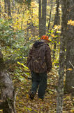 Senior hunter on the deer track. Senior hunter walking on the deer track by an Autumn day. Great atmosphere scene, Quebec. Canada Royalty Free Stock Photography