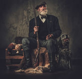 Senior hunter with a english setter and shotgun in a traditional shooting clothing, sitting on a dark background. Royalty Free Stock Photos