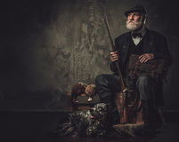 Senior hunter with a english setter and shotgun in a traditional shooting clothing, sitting on a dark background. Stock Photos