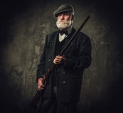 Senior hunter with a shotgun in a traditional shooting clothing, posing on a dark background. Stock Photos