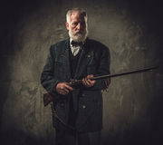 Senior hunter with a shotgun in a traditional shooting clothing, posing on a dark background. Stock Photography