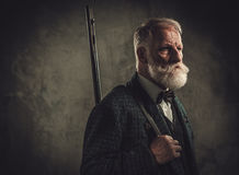 Senior hunter with a shotgun in a traditional shooting clothing, posing on a dark background. Royalty Free Stock Photos