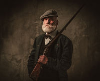Senior hunter with a shotgun in a traditional shooting clothing, posing on a dark background. Stock Images