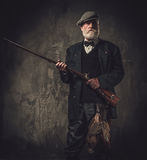 Senior hunter with a shotgun in a traditional shooting clothing, posing on a dark background Royalty Free Stock Image