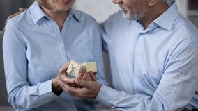 Senior husband giving present to wife, woman delighted with precious gift royalty free stock photo