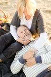 Senior husband lying on wife knees, sand beach in background. stock image