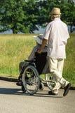 Senior husband pushing wife in wheelchair Stock Photos