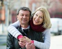 Senior husband and wife cuddling outdoors Stock Image