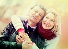 Senior husband and wife cuddling outdoors Royalty Free Stock Photo