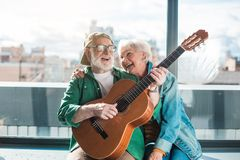 Senior husband and wife looking amused with guitar. Musical holiday. Waist up portrait of amorous married men and women enjoying playing on instrument stock photos