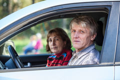 Senior husband and wife sitting in land vehicle, looking through the window Stock Images