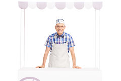 Senior ice cream seller standing behind an ice cream stand Stock Photos
