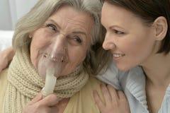 Senior ill woman with caring daughter. Senior ill women with caring daughter at home Stock Image