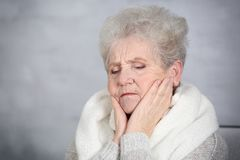 Senior ill woman with sore throat on grey background Stock Photo