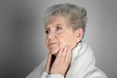 Senior ill woman with sore throat on grey background Stock Photos