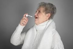 Senior ill woman using spray on grey background. Concept of allergy royalty free stock image
