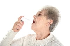 Senior ill woman using spray, isolated on white. Concept of allergy royalty free stock image