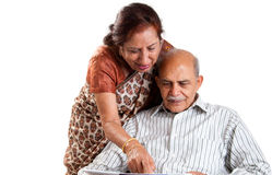 Senior Indian couple. A senior Indian / Asian couple pointing at a newspaper - isolated on white Royalty Free Stock Photos