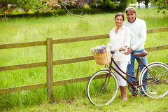 Senior Indian Couple On Cycle Ride In Countryside. Looking At Camera Smiling Stock Photography
