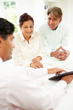 Senior Indian Couple Meeting With Financial Advisor At Home. Having Discussion Stock Image