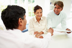Senior Indian Couple Meeting With Financial Advisor At Home. In Kitchen Shaking Hands Royalty Free Stock Photography