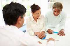 Senior Indian Couple Meeting With Financial Advisor At Home. Signing Documents Stock Photos