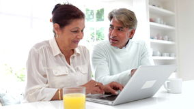 Senior Indian Couple Using Laptop Computer At Home. Senior Asian Indian couple sitting at kitchen counter using laptop computer and talking.Shot on Canon 5d Mk2 stock footage