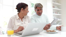 Senior Indian Couple Using Laptop And Digital Tablet At Home. Senior Asian Indian couple sitting at kitchen counter using laptop and digital tablet whilst eating stock footage