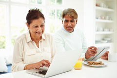 Senior Indian Couple Using Laptop And Digital Tablet At Home. Sitting At Dining Table Royalty Free Stock Photo