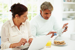 Senior Indian Couple Using Laptop And Digital Tablet At Home Royalty Free Stock Images