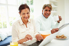 Senior Indian Couple Using Laptop And Digital Tablet At Home Stock Images