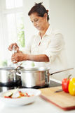 Senior Indian Woman Cooking Meal At Home. In Kitchen Concentrating Stock Photos