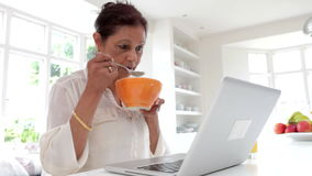 Senior Indian Woman Using Laptop Whilst Eating Breakfast stock footage