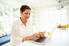 Senior Indian Woman Using Laptop Whilst Eating Breakfast. In Kitchen Stock Photo