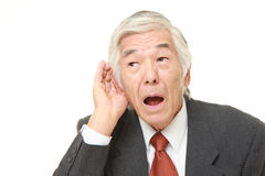 Senior Japanese businessman with hand behind ear listening closely Royalty Free Stock Photo