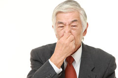 Senior Japanese businessman holding his nose because of a bad smell. Studio shot of senior Japanese businessman on white background royalty free stock photos
