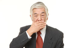 Senior Japanese businessman making the speak no evil gesture Royalty Free Stock Image