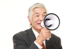 Senior Japanese businessman with megaphone. Studio shot of senior Japanese businessman on white background Stock Photography