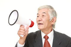 Senior Japanese businessman with megaphone. Studio shot of senior Japanese businessman on white background Stock Images