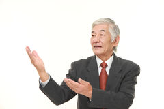 Senior Japanese businessman presenting and showing something Stock Photo