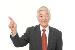 Senior Japanese businessman presenting and showing something Royalty Free Stock Image