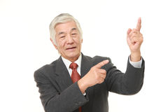 Senior Japanese businessman presenting and showing something Royalty Free Stock Photos